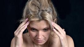 Печальная женщина держится руками за голову