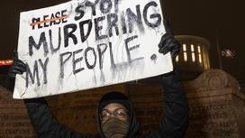 """Протестующий с плакатом """"Хватит убивать моих людей"""""""