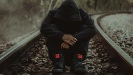 Мужчина сидит на железнодорожных путях