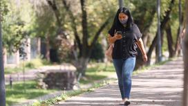 Женщина смотрит в телефон и идет по улице
