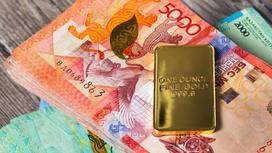 Золотой слиток лежит на пачке денег