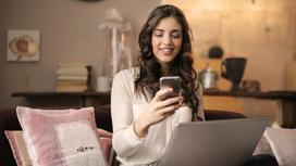 Девушка с телефоном в руках сидит перед компьютером