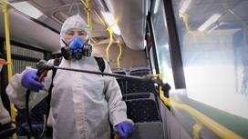 Дезинфектор разбрызгивает дезраствор на поручни автобуса