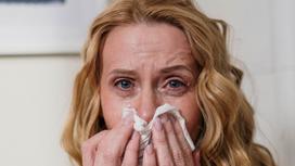 Женщина держит носовой платок у носа