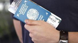 Мужчина держит в руке паспорт и билет