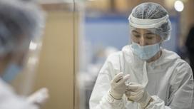 Медик набирает в шприц препарат для вакцинации