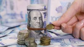 Сверток долларов на фоне тенге
