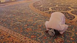 мужчина молится в мечети