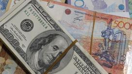 пачки тенге и долларов лежат на столе