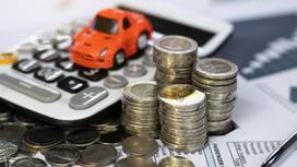 Игрушечная машинка стоит на калькуляторе рядом со стопками монет