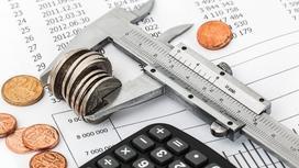Монеты зажаты в измерительном инструменте, который лежит на графике платежей рядом с калькулятором