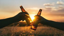 Двое с бутылками пива на фоне заката