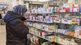 Женщина стоит у полки с лекарствами