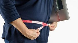 Человек измеряет талию с весами в руках