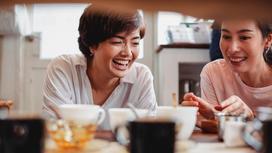 Две женщины смеются, сидя за обеденным столом
