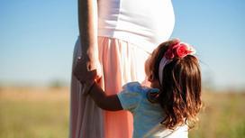 Женщина стоит с ребенком