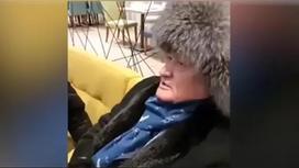 Мужчина в шапке сидит на диване