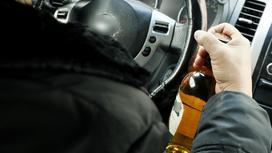 Мужчина пьет за рулем