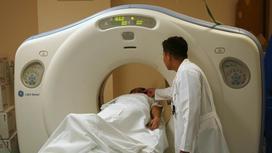 Врач готовит пациента к компьютерной томографии
