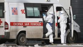 Медики в защитных костюмах стоят рядом с машиной скорой помощи