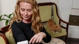 Женщина чистит одежду возле кошки