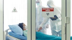 Двое медиков стоят у больничной койки пациентки за закрытыми дверями
