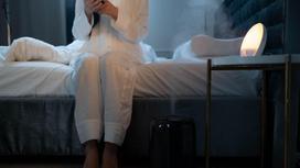 Девушка сидит на кровати, рядом стоит увлажнитель воздуха