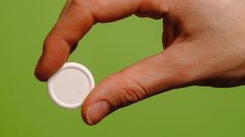 Круглая таблетка в руках