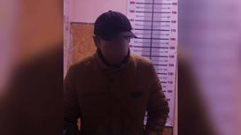 Подозреваемый в преступлении стоит у ростомера в верхней одежде