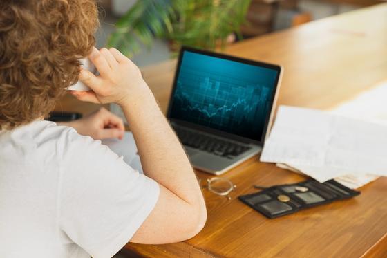 парень сидит за столом и смотрит в ноутбук