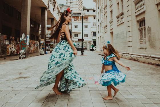 Босая девушка в цветастой юбке танцует на улице вместе с маленькой девочкой