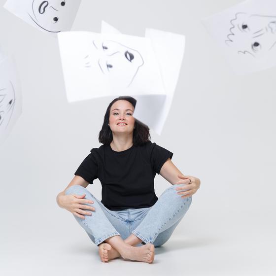 Женщина улыбается на фоне рисунков лиц с разными эмоциями
