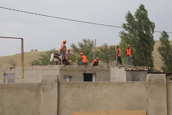 Строители ремонтируют дом