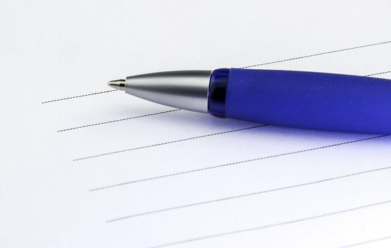 Ручка лежит на бумаге со строками