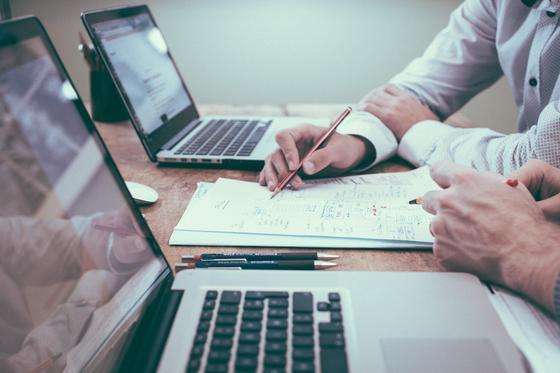 Бизнес-консультант работает за ноутбуком и с бумагами