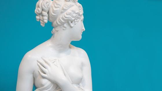 Женская скульптура из белого камня на голубом фоне