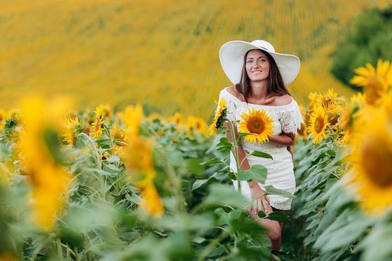 Девушка в белом платье и шляпе среди подсолнухов