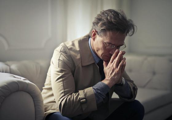 Мужчина в очках сидит на диване, закрыв лицо руками