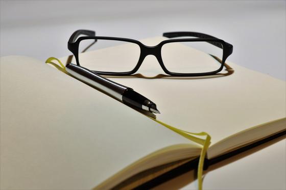 Очки и ручка на раскрытом блокноте