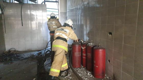 Пожарные выносят баллоны