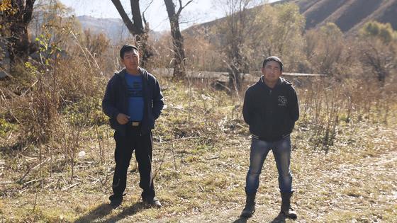 Двое мужчин стоят на дороге