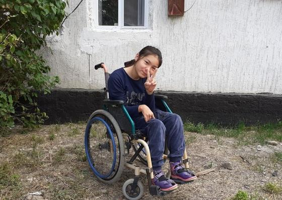 Девочка сидит в инвалидном кресле возле дома
