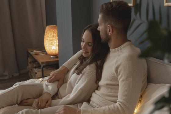 Мужчина и женщина обнимаются, сидя в кровати