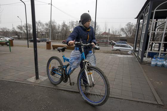 Мальчик везет бутылки на велосипеде