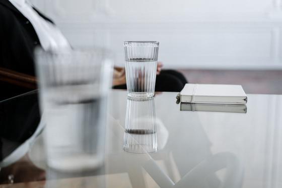 Стаканы с водой и блокнот на столе