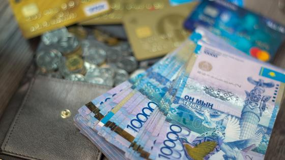 Пачка тенге лежит на кошельке среди монет и банковских карт