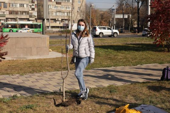 Девушка в серой куртке стоит у дерева