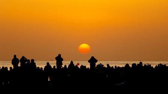 Люди встречают рассвет возле моря