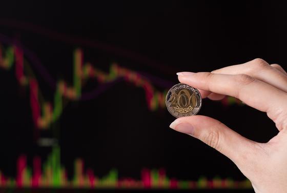 Женщина держит монету тенге на фоне электронного графика