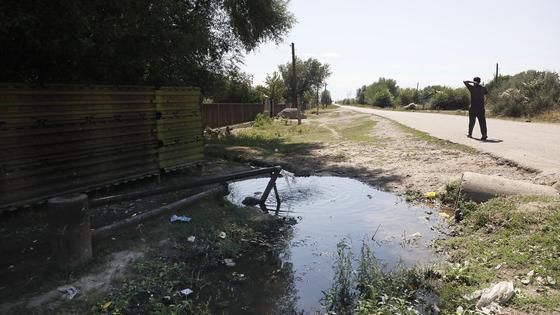 Мужчина идет по дороге возле колонки с водой